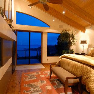 Imagen de dormitorio principal, contemporáneo, grande, con paredes beige, suelo de madera en tonos medios, chimenea lineal y marco de chimenea de metal