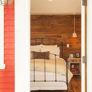 Cette image montre une chambre parentale craftsman de taille moyenne avec un mur beige et un sol en bois brun.