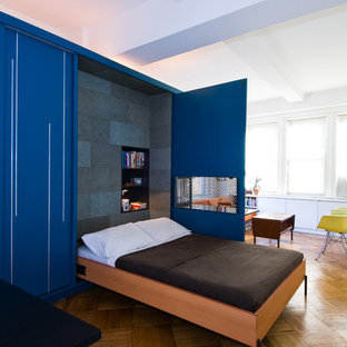 Example of a trendy medium tone wood floor bedroom design in New York with blue walls