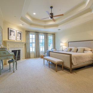 Modelo de dormitorio principal, tradicional, grande, con paredes beige, moqueta, chimenea tradicional, marco de chimenea de madera y suelo beige