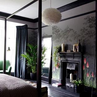 Mittelgroßes Stilmix Gästezimmer mit bunten Wänden, gebeiztem Holzboden, Kamin, Kaminumrandung aus Metall und schwarzem Boden in Sonstige