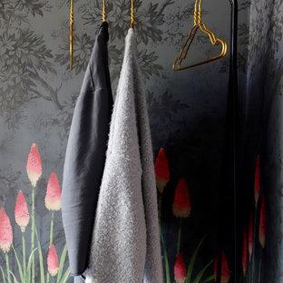 Foto di una camera degli ospiti boho chic di medie dimensioni con pareti multicolore, pavimento in legno verniciato, camino classico, cornice del camino in metallo e pavimento nero