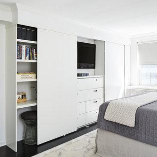 Mid-sized minimalist master dark wood floor and black floor bedroom photo in New York with white walls