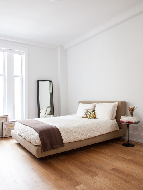 Inspiration for a contemporary medium tone wood floor bedroom remodel in  New York with white walls