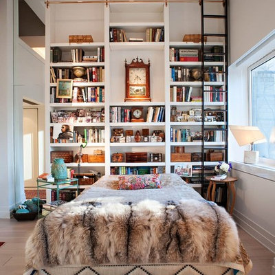 Inspiration for an eclectic light wood floor bedroom remodel in New York with white walls and no fireplace