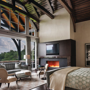 This is an example of a large contemporary master bedroom in New York with beige walls, dark hardwood floors, a standard fireplace, a metal fireplace surround and brown floor.