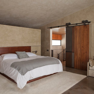 Photo of a large modern loft-style bedroom in New York with beige walls, limestone floors and no fireplace.