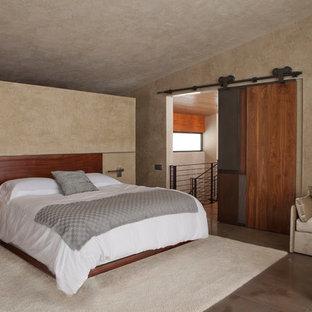 Imagen de dormitorio tipo loft, minimalista, grande, sin chimenea, con paredes beige y suelo de piedra caliza