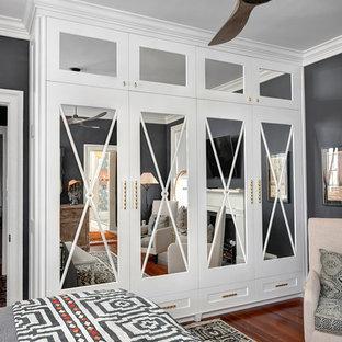 Пример оригинального дизайна: хозяйская спальня среднего размера в современном стиле с серыми стенами, темным паркетным полом, стандартным камином, фасадом камина из дерева и коричневым полом