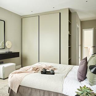 Photo of a medium sized contemporary guest bedroom in London with no fireplace, beige floors, light hardwood flooring and grey walls.