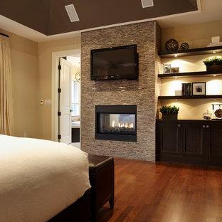 トロントの広いコンテンポラリースタイルのおしゃれな主寝室 (ベージュの壁、無垢フローリング、両方向型暖炉、石材の暖炉まわり) のレイアウト