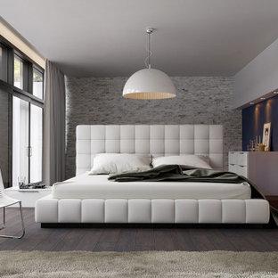 Diseño de dormitorio principal, industrial, de tamaño medio, con paredes grises, suelo de madera clara, chimenea de esquina, marco de chimenea de piedra y suelo gris