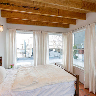 Design ideas for an industrial bedroom in Seattle with white walls and terra-cotta floors.