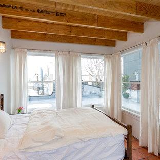 Diseño de dormitorio urbano con paredes blancas y suelo de baldosas de terracota