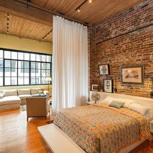 Foto på ett stort industriellt sovrum, med mellanmörkt trägolv