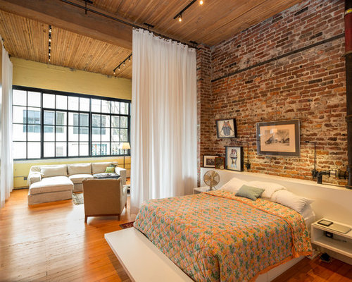 Example Of A Large Urban Medium Tone Wood Floor Bedroom Design In Seattle