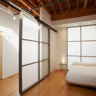 Foto på ett industriellt sovrum, med vita väggar och bambugolv