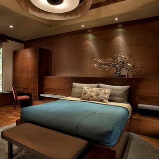 Example of a large trendy master dark wood floor bedroom design in Phoenix with brown walls and no fireplace