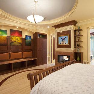 Ejemplo de dormitorio principal, bohemio, grande, con suelo de madera clara, chimenea de doble cara y marco de chimenea de piedra