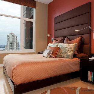 Modelo de dormitorio principal, contemporáneo, grande, sin chimenea, con paredes rojas y suelo de madera clara