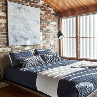 Industrial master bedroom in Sydney with dark hardwood floors and brown floor.