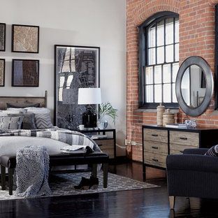 Design ideas for a mid-sized industrial loft-style bedroom in New York with white walls, light hardwood floors, no fireplace and beige floor.
