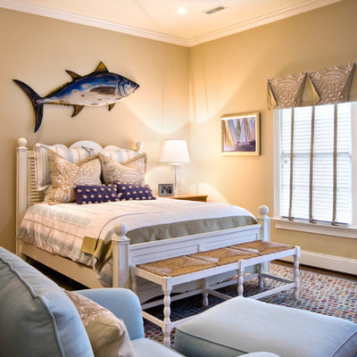 Example of a large beach style guest dark wood floor and brown floor bedroom design in Charleston with beige walls