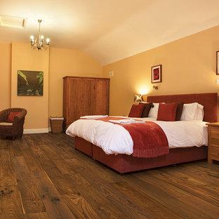 Modelo de dormitorio principal, de estilo americano, de tamaño medio, sin chimenea, con paredes beige y suelo de madera oscura