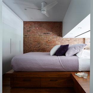 Modelo de dormitorio tipo loft, minimalista, pequeño, sin chimenea, con paredes blancas, suelo de madera en tonos medios y suelo azul