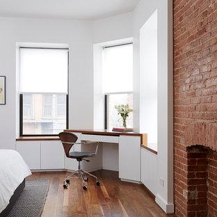 Foto de dormitorio principal, moderno, de tamaño medio, con paredes blancas, suelo de madera en tonos medios, chimenea tradicional y marco de chimenea de ladrillo