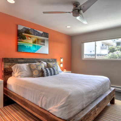 Example of an island style bedroom design in Orange County with orange walls