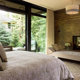 Inspiration för ett funkis sovrum, med en dubbelsidig öppen spis och en spiselkrans i sten