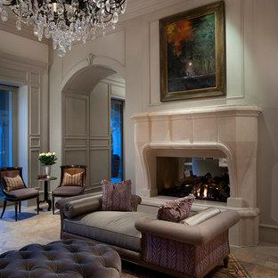 Ispirazione per un'ampia camera matrimoniale moderna con pareti beige, camino bifacciale, cornice del camino in pietra, pavimento in travertino e pavimento beige