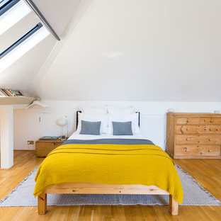 This is an example of a scandinavian loft-style bedroom in London with white walls, medium hardwood floors and no fireplace.