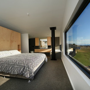 This is an example of a mid-sized contemporary master bedroom in Sydney with carpet, no fireplace and white walls.