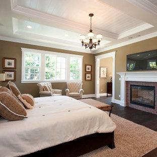 Imagen de dormitorio tradicional con paredes marrones, suelo de madera oscura, chimenea tradicional y marco de chimenea de ladrillo