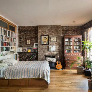 Modelo de dormitorio tipo loft, industrial, pequeño, con suelo de madera clara, estufa de leña y marco de chimenea de ladrillo