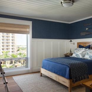 Aménagement d'une chambre d'amis bord de mer de taille moyenne avec un mur bleu, un sol en bois brun, aucune cheminée, un sol marron, un plafond en lambris de bois et boiseries.