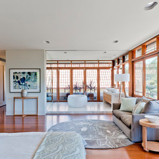 Design ideas for a large contemporary master bedroom in Sydney with white walls, medium hardwood floors and brown floor.
