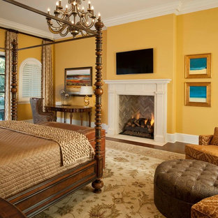 This is an example of a large mediterranean bedroom in Other with yellow walls, dark hardwood floors, a standard fireplace and brown floor.