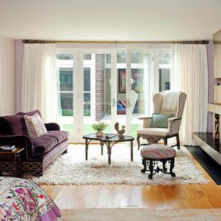 Diseño de dormitorio principal, bohemio, grande, con marco de chimenea de hormigón, paredes púrpuras, suelo de madera clara y chimenea de esquina
