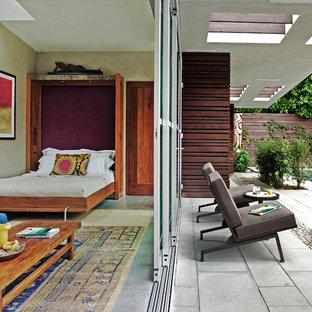 Ispirazione per una camera degli ospiti eclettica di medie dimensioni con pareti beige, pavimento in cemento e nessun camino