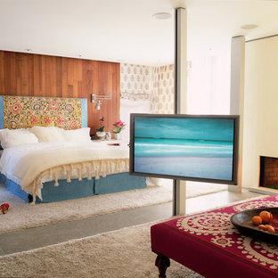 Идея дизайна: большая хозяйская спальня в современном стиле с бежевыми стенами, бетонным полом, стандартным камином и фасадом камина из штукатурки