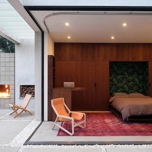 Immagine di una camera degli ospiti minimalista con pareti bianche, pavimento in cemento e pavimento grigio