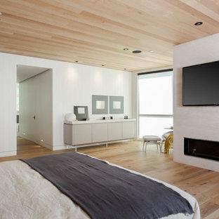 Imagen de dormitorio principal, ecléctico, grande, con paredes blancas, suelo de bambú, chimenea lineal, marco de chimenea de yeso y suelo beige