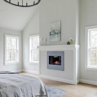 Modelo de dormitorio principal, de estilo de casa de campo, de tamaño medio, con paredes grises, suelo de madera clara, chimenea tradicional y marco de chimenea de yeso
