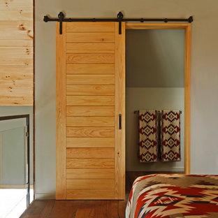 Diseño de dormitorio principal, rural, de tamaño medio, sin chimenea, con paredes marrones, suelo de madera en tonos medios y suelo marrón