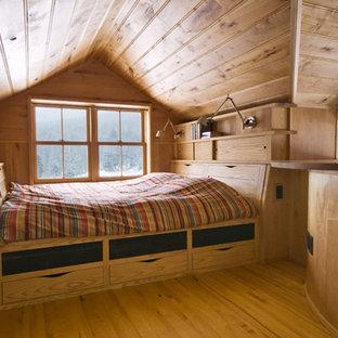 Example of a mid-sized trendy guest light wood floor bedroom design in Burlington with beige walls