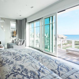 Inspiration for a large coastal master marble floor and gray floor bedroom remodel in Other with gray walls, a standard fireplace and a plaster fireplace