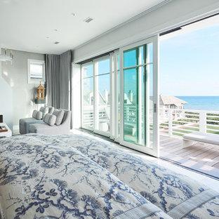 На фото: большая хозяйская спальня в морском стиле с серыми стенами, мраморным полом, стандартным камином, фасадом камина из штукатурки и серым полом с